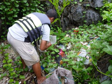 Mang Jun picks up trash entangled in beach plants