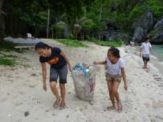 Rhona and Dulce carry a full sack back to the boat